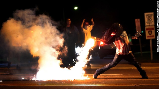 A protester throws a tear gas canister back toward police on August 13.