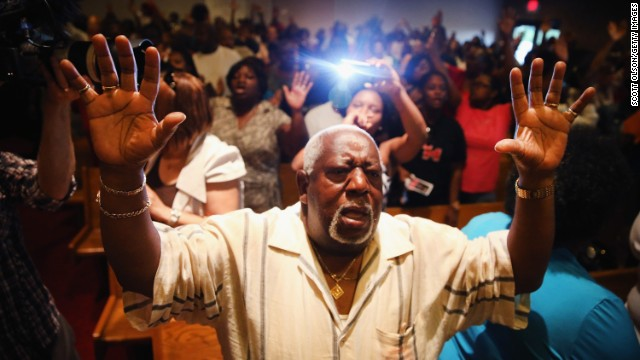 People congregate at the Greater St. Marks Family Church in St. Louis along with the family of Michael Brown and the Rev. Al Sharpton on August 12.