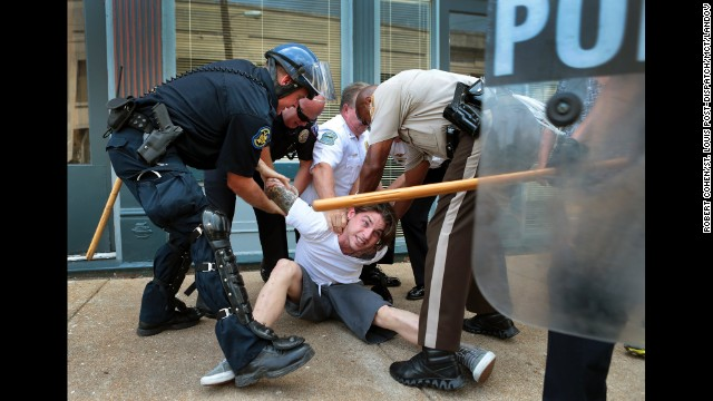 Police officers arrest a man who refused to leave when police cleared streets in Ferguson on August 11.