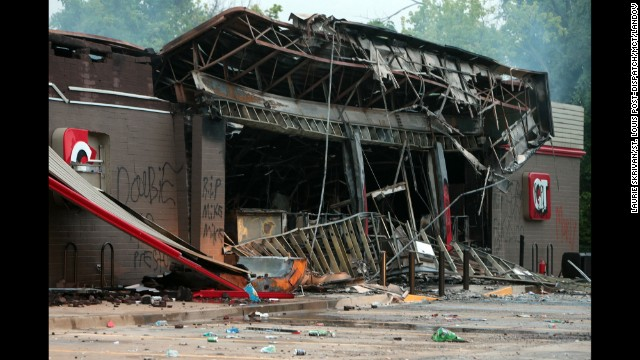 A burned-out QuikTrip gas station smolders on August 11 after protesters looted and burned the Ferguson building the night before.