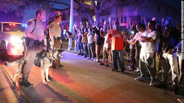 Police officers and protesters confront each other in Ferguson, Missouri, on Monday, August 9. The St. Louis suburb <a href='http://www.cnn.com/2014/08/14/us/gallery/ferguson-missouri-protests/index.html'>has been in turmoil</a> since Darren Wilson, a white police officer, fatally shot Michael Brown, an unarmed black teenager, on August 9. Some protesters and law enforcement officers have clashed in the streets, leading to injuries and arrests. Photographs have given a face to causes during protests throughout history. Click through to see some of those images.