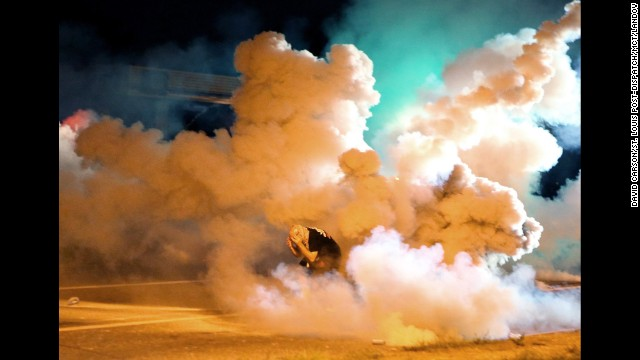 A protester runs from tear gas exploding around him on August 13.