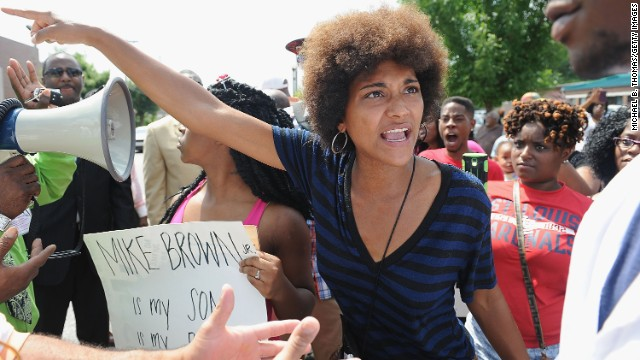 A woman tries to calm an emotional protester during a demonstration outside the headquarters of the Ferguson Police Department on August 11.