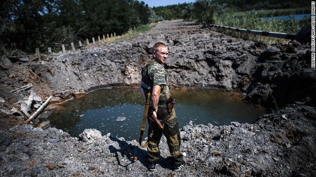 A pro-Russian gunman stands next a bomb crater after shelling near Donetsk on Thursday.
