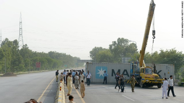 Pakistani policemen block the motorway which links Lahore and Peshawar to the capital Islamabad on August 13.