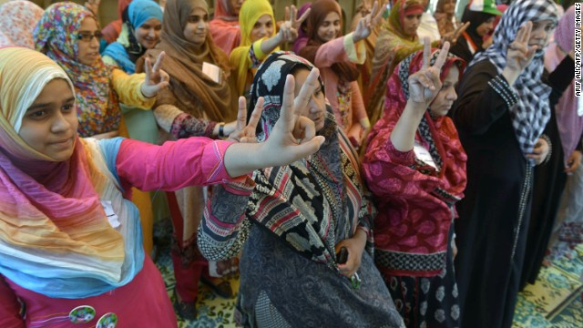 Supporters of cleric Tahir ul Qadri flash the victory sign outside his home in Lahore on August 13.