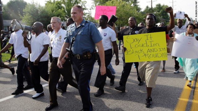 Thousands of demonstrators march down a Ferguson street with members of the St. Louis County Police and the Missouri State Highway Patrol on Thursday, August 14.