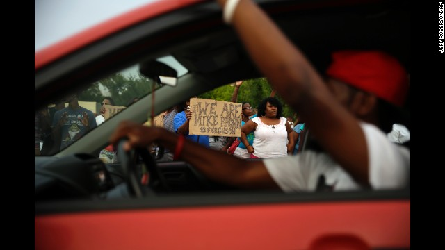 Demonstrators hold signs as traffic moves slowly past them on August 14.