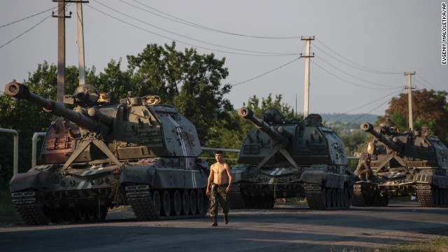 A Ukrainian soldier walks past a line of self-propelled guns as a column of military vehicles prepares to head to the front line near Ilovaisk, Ukraine, on Thursday, August 14.