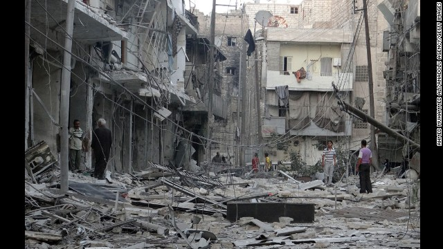 Residents inspect the rubble of destroyed buildings in Aleppo after Syrian regime helicopters allegedly dropped barrel bombs there on Wednesday, August 13.
