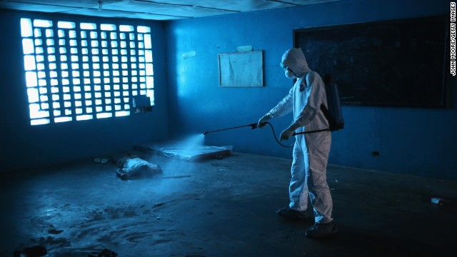 A health worker disinfects a corpse after a man died in a classroom being used as an Ebola isolation ward Friday, August 15, in Monrovia.