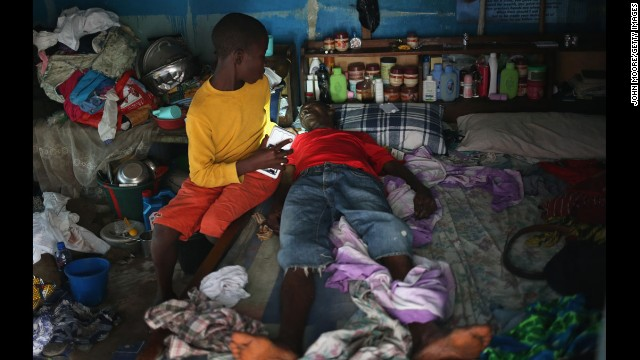 A boy tries to prepare his father before they are taken to an Ebola isolation ward August 15 in Monrovia.