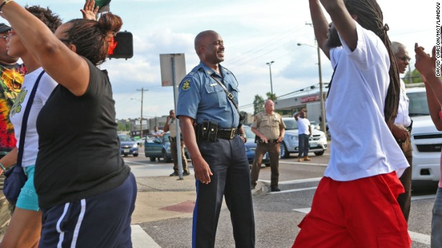State Highway Patrol Capt. Ron Johnson smiles at demonstrators on August 14. Johnson was appointed to lead security as state troopers took over after days of clashes between protesters and local police.