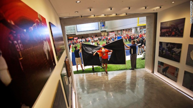 Fans run through a banner to be the first to tour the Hall of Fame. The 94,000-square-foot facility features a 150-seat theater and a 45-yard football field.