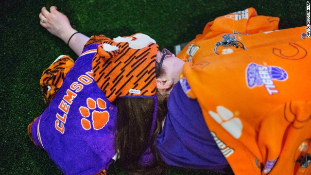 "Clemson fan Amelia Stefanelli sleeps on a turf football field at the Hall of Fame. After touring the exhibits, guests were served dinner on the field before settling in for the night as college football-themed movies such as ""Rudy"" played."
