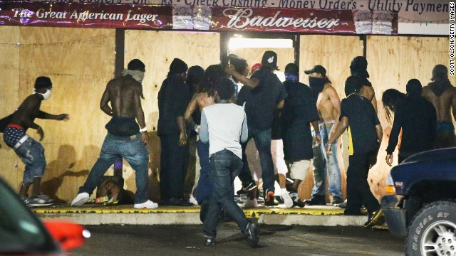 People loot the Ferguson Market and Liquor store on August 16. Several businesses were looted as police held their positions nearby.