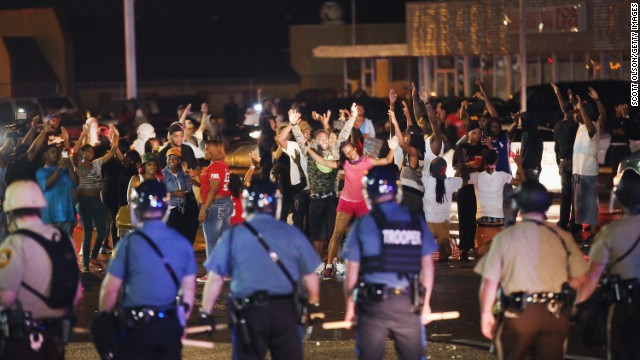 Missouri State Highway Patrol officers listen to taunts from demonstrators during a protest on Friday, August 15.