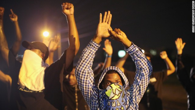 "Demonstrators protest with their hands up on August 15. The ""hands up"" gesture has become a symbol in protests as Brown, according to eyewitnesses, was trying to surrender when he was shot multiple times."