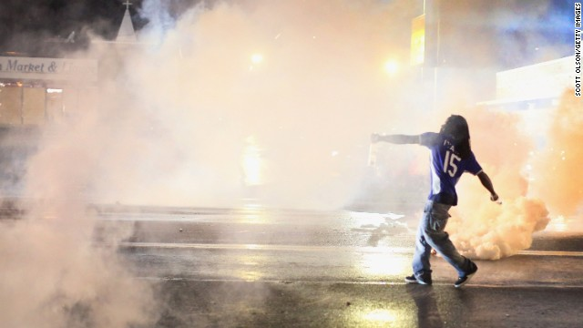 A demonstrator throws a tear gas canister back at police on August 15.