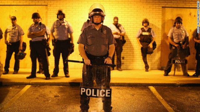 Police stand guard before the midnight curfew on Saturday, August 16.