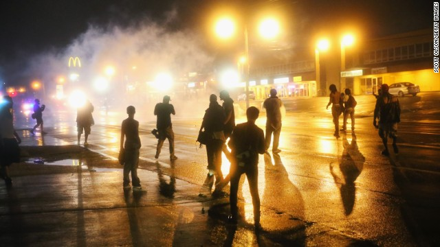 Police fire tear gas at demonstrators after curfew on August 17.