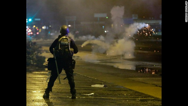 A law enforcement officer watches as tear gas is fired to disperse a crowd on August 17.