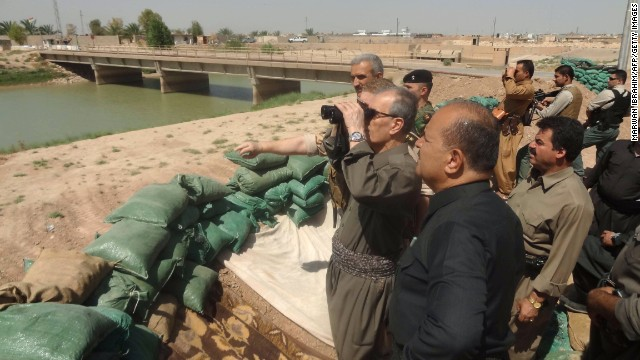 The governor of Kirkuk and head of the security committee, Najm al-Din Omar, looks through binoculars toward Islamist Jihadist positions on August 17 from a position manned by the Kurdish Peshmerga south of the oil hub city of Kirkuk.