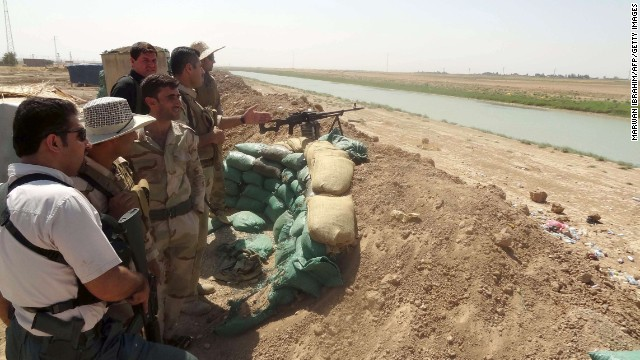 Kurdish Peshmerga fighters stand behind a sand barricade set up close to the village of Bashir on August 17.