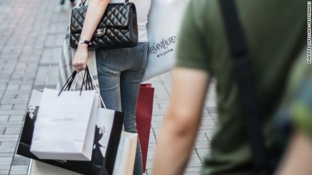 A woman carries luxury shopping bags in Hong Kong.