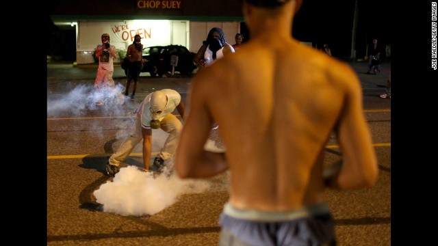 A protester picks up a tear gas canister on Sunday, August 17.
