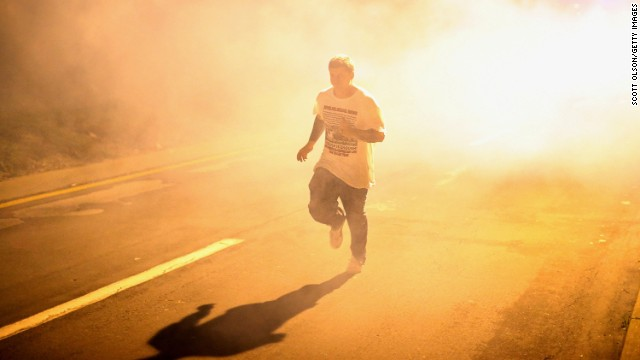 A man runs through clouds of tear gas on August 17.