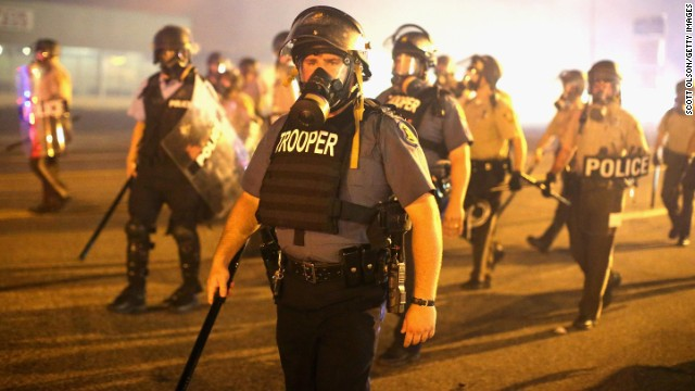 Police advance through a cloud of tear gas on August 17. Most of the crowd had dispersed after a curfew went into effect at midnight, St. Louis County authorities said.
