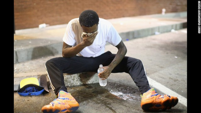 A man fights the effects of tear gas in Ferguson on August 17.
