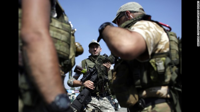 Ukrainian soldiers carry weapons at a checkpoint near Debaltseve, Ukraine, on Saturday, August 16.