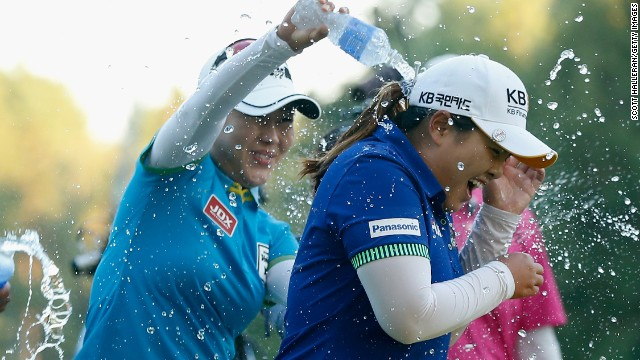 Meena Lee (L) sprays water on Inbee Park after the South Korea beats Brittany Lincicome on the first playoff hole at Monroe Golf Club.