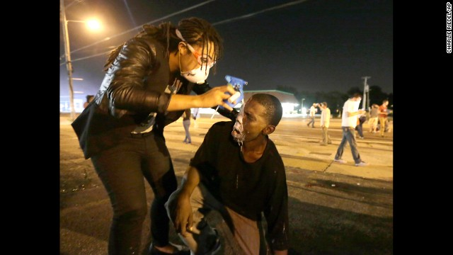 A woman helps a man affected by tear gas August 18. The situation overnight deteriorated after a handful of protesters threw