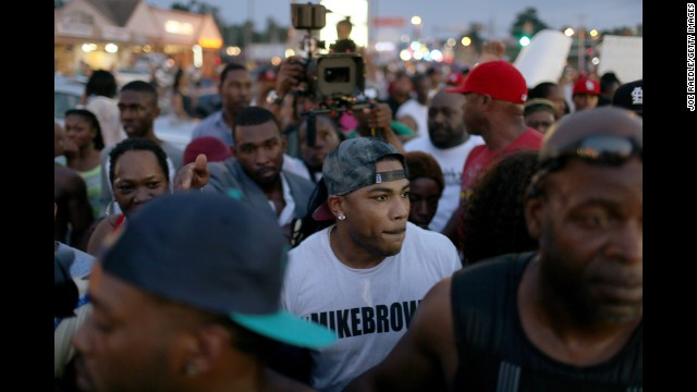 Musician Nelly, center, joins demonstrators in Ferguson on August 18.