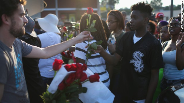 Demonstrators receive red roses as they protest August 18.