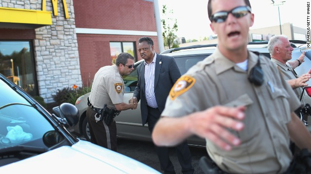 The Rev. Jesse Jackson shakes hands with a police officer as he visits Ferguson's demonstration area on August 18.