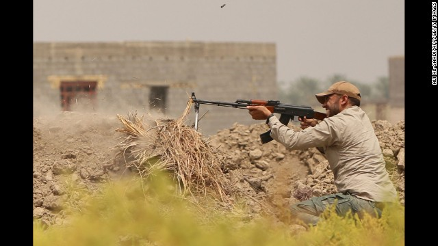 A Shiite fighter defends a post while backing the Iraqi army in its fight against ISIS militants south of Baghdad on August 18.