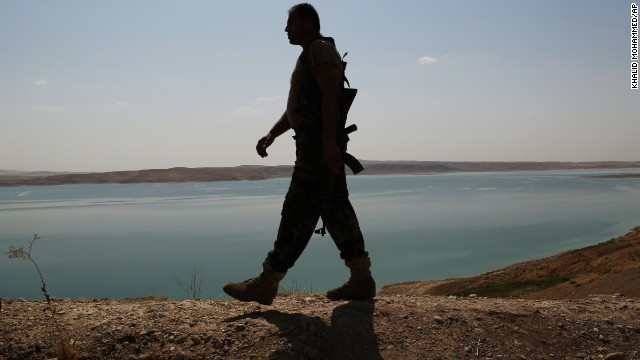 A Kurdish Peshmerga fighter patrols near the Mosul Dam in Chamibarakat, Iraq, on Sunday, August 17.