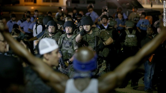 Police point out a demonstrator who has his arms raised before moving in to arrest him Tuesday, August 19.
