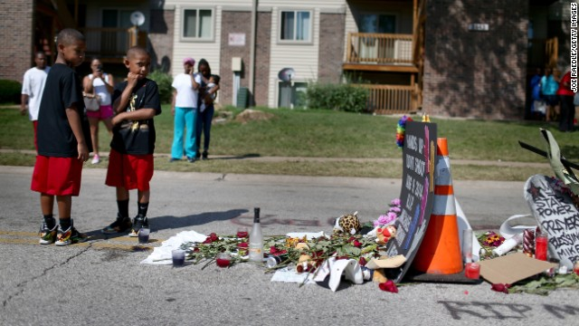 People on August 19 stand near a memorial where Brown was shot and killed.