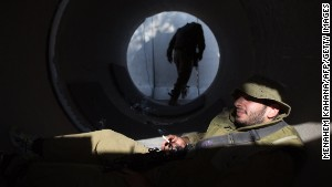 An Israeli soldier smokes a cigarette as he sits in a large concrete pipe used as shelter at an army deployment point near the Israeli-Gaza border on Wednesday, August 20.