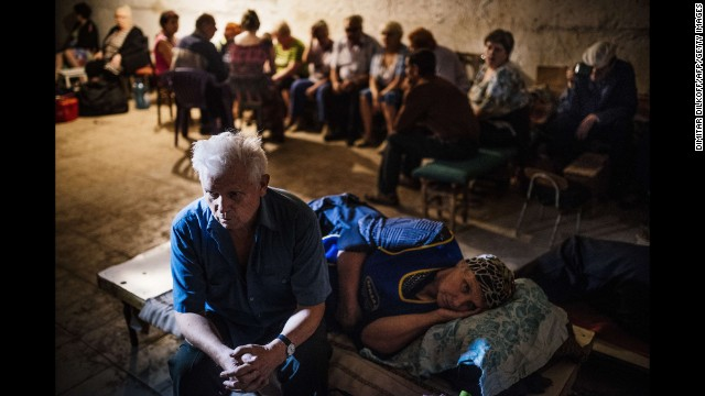 Residents sit in a makeshift bomb shelter during a shelling in Makiyivka, Ukraine, on Wednesday, August 20.