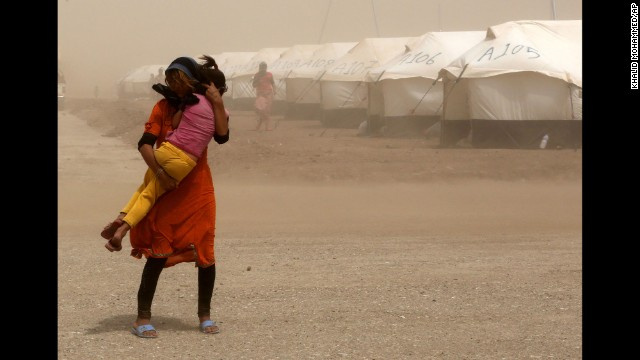 A woman holds her sister during a sandstorm at a refugee camp in Feeshkhabour on August 19.