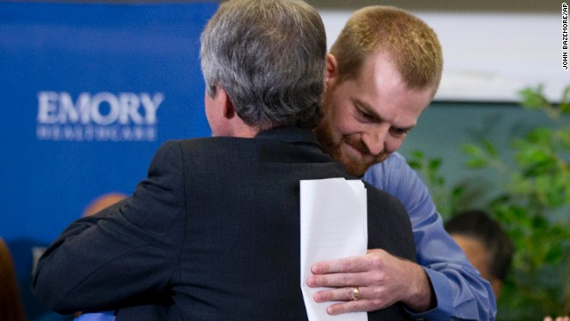 Ebola survivor Dr. Kent Brantly, right, hugs a member of the Emory University Hospital staff after being released from treatment in Atlanta on August 21.