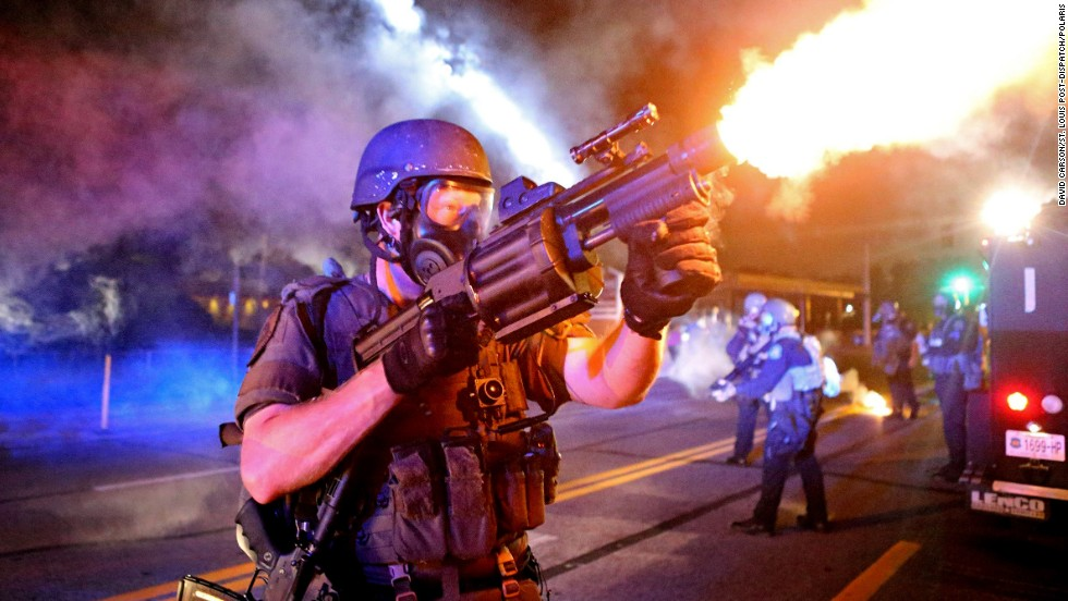 A law enforcement officer fires tear gas in the direction where bottles were thrown from crowds Monday, August 18, in Ferguson, Missouri. The St. Louis suburb <a href='http://www.cnn.com/2014/08/14/us/gallery/ferguson-missouri-protests/index.html'>has been in turmoil</a> since Darren Wilson, a white police officer, fatally shot Michael Brown, an unarmed black teenager, on August 9. Some protesters and law enforcement officers have clashed in the streets, leading to injuries and arrests.