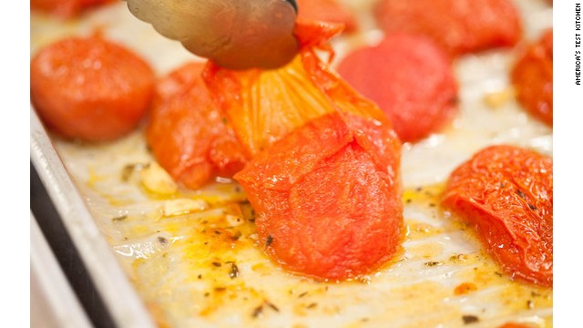 Use tongs to remove and discard the hot tomato skins, and then return the tomatoes to the oven. After 1 hour (be sure to keep siphoning off any remaining liquid), use a spatula to flip the tomato pieces cut-side up for the remainder of cooking.