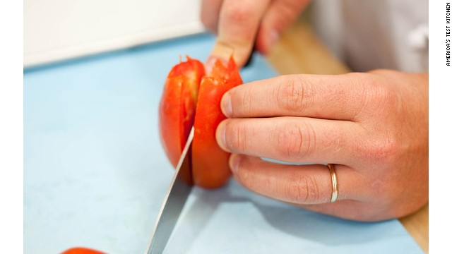 Once the tomatoes are cored, halve them through the core with a chef's or serrated knife. Don't remove the seeds or jelly-like pulp, though, because they both contain a lot of flavor.